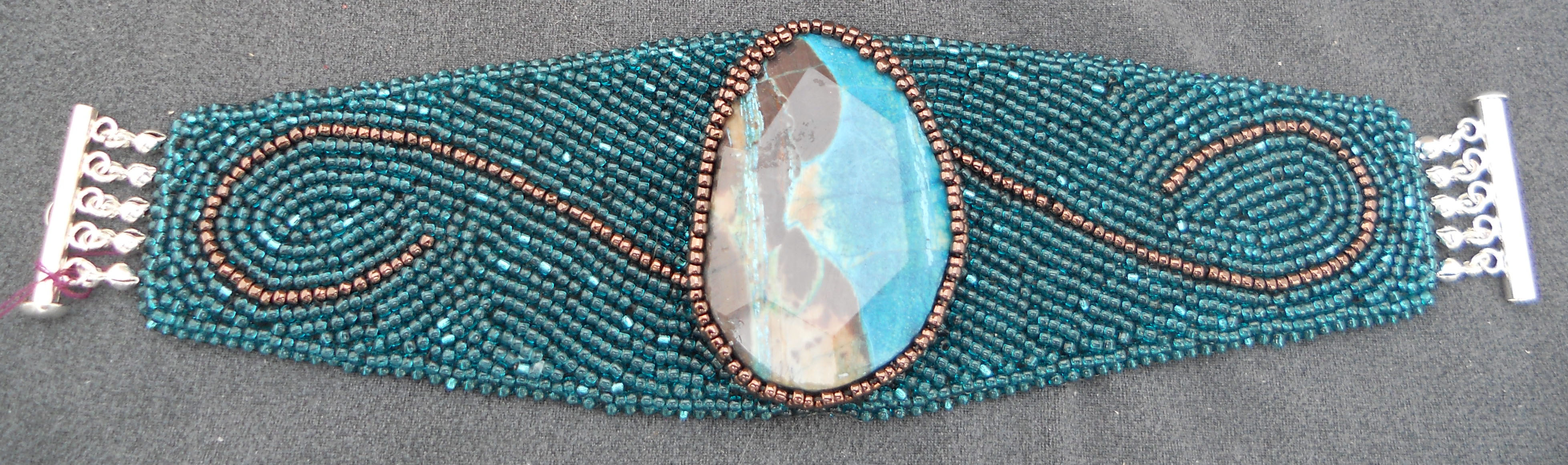picture of bracelet using a freeform slab chrysocolla cabochon as focal  stone. The bracelet is